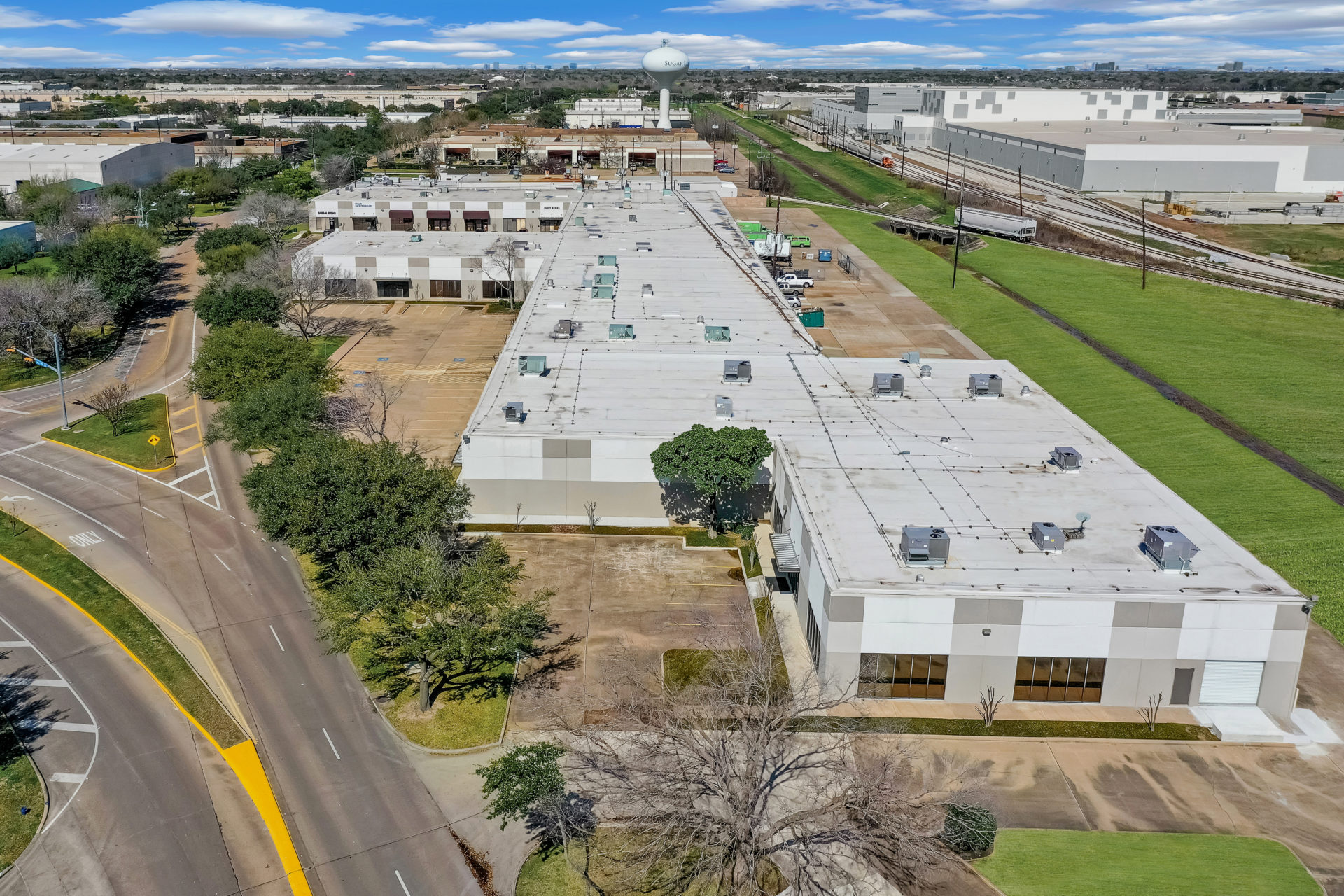 Overhead view of 700 Industrial Boulevard showcasing the roof, parking lot, and entire length of the building